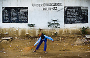 8th August 2014, Shakarpur, New Delhi, India. A boy sweeps the ground in front of the blackboards before class begins at a makeshift school under a metro bridge near the Yamuna Bank Metro station in Shakarpur, New Delhi, India on the 8th August 2014<br /> <br /> Rajesh Kumar Sharma (born 01/02/1970), started this makeshift school in 2011. Six mornings a week he teaches underprivileged children for three hours while his younger brother replaces him at his general store in Shakarpur. His students are children of labourers, rickshaw-pullers and farm workers. This is the 3rd site he has used to teach under privileged children in the city, he began in 1997. <br /> <br /> PHOTOGRAPH BY AND COPYRIGHT OF SIMON DE TREY-WHITE<br /> + 91 98103 99809<br /> email: simon@simondetreywhite.com<br /> photographer in delhi<br /> journalist