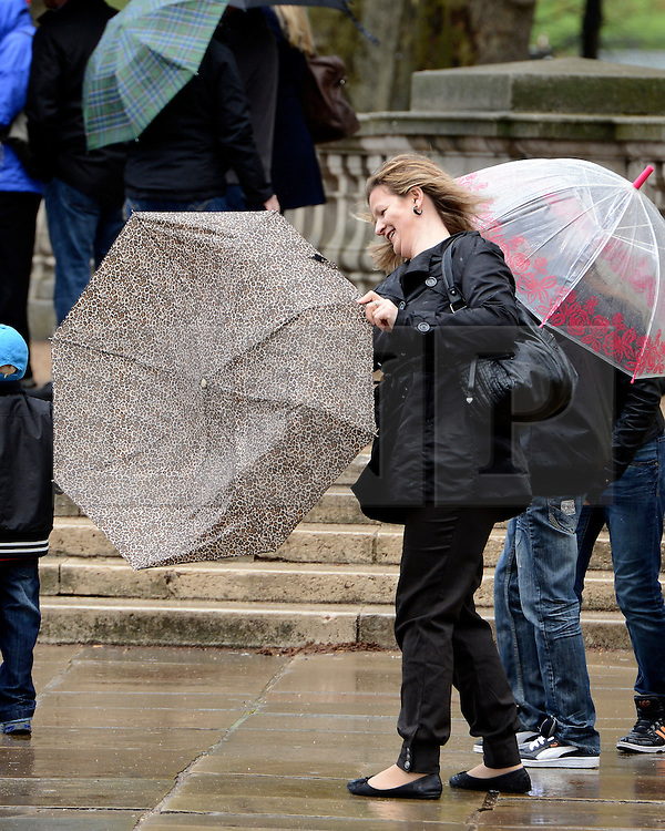 © Licensed to London News Pictures. 26/04/2012. London, UK . Tourists battle with the wind and rain near Buckingham Palace today 26th April 2012. Photo credit : Stephen Simpson/LNP