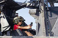 New Windsor, New York - A young boy wears a helmet while sitting at the controls of a military helicopter on display at the New York Air Show at Stewart International Airport on Aug. 29, 2015.