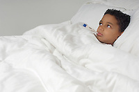 Boy (7-9) with thermometer in mouth, lying in bed