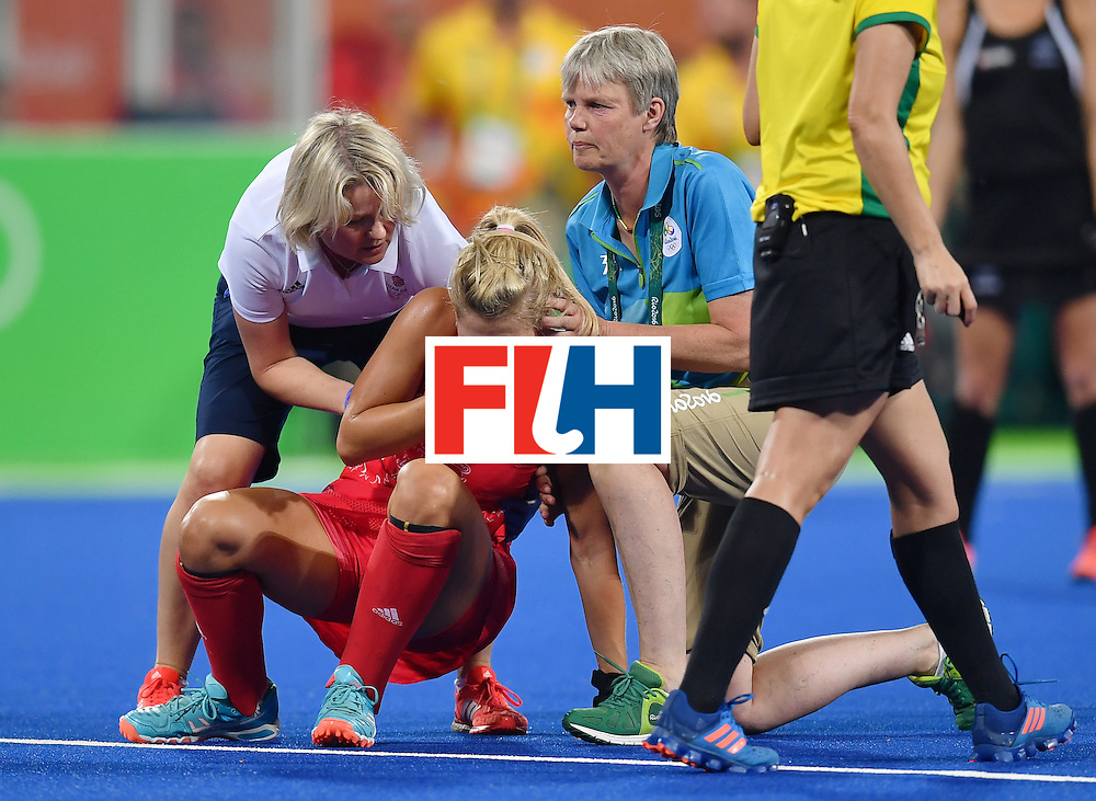 Britain's Georgie Twigg is helped to get up after resulting injuried during the women's semifinal field hockey New Zealand vs Britain match of the Rio 2016 Olympics Games at the Olympic Hockey Centre in Rio de Janeiro on August 17, 2016. / AFP / MANAN VATSYAYANA        (Photo credit should read MANAN VATSYAYANA/AFP/Getty Images)