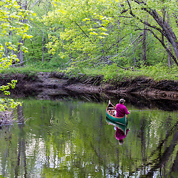 A man canoeing and fishing in spring on the Lamprey River in Epping, New Hampshire.