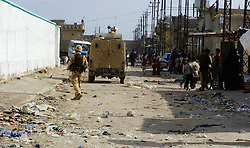 British soldiers from the Duke of Wellington's Regiment wearing desert camouflage, and body armor, carrying SA80 assault rifles which are fitted with SUSAT sights,on a foot patrol through the streets of a viliage near Shia Flats gathering low level intelligence through speaking with locals, during Op-Telic in March 2005.