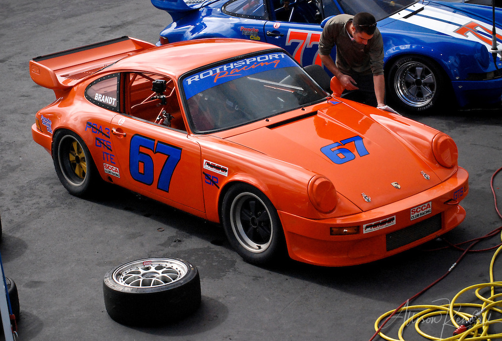 An orange Porsche is prepped for racing during SCCA events at Laguna Seca