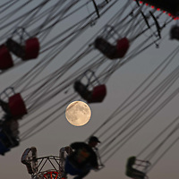 The full moon rises as riders take a spin on the Wave Swinger during the Oregon State Fair on Thursday, Aug. 30, 2012.