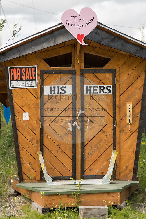 A for sale sign on a his and her outhouse in a rural section of Alaska outside Fairbanks, Alaska.