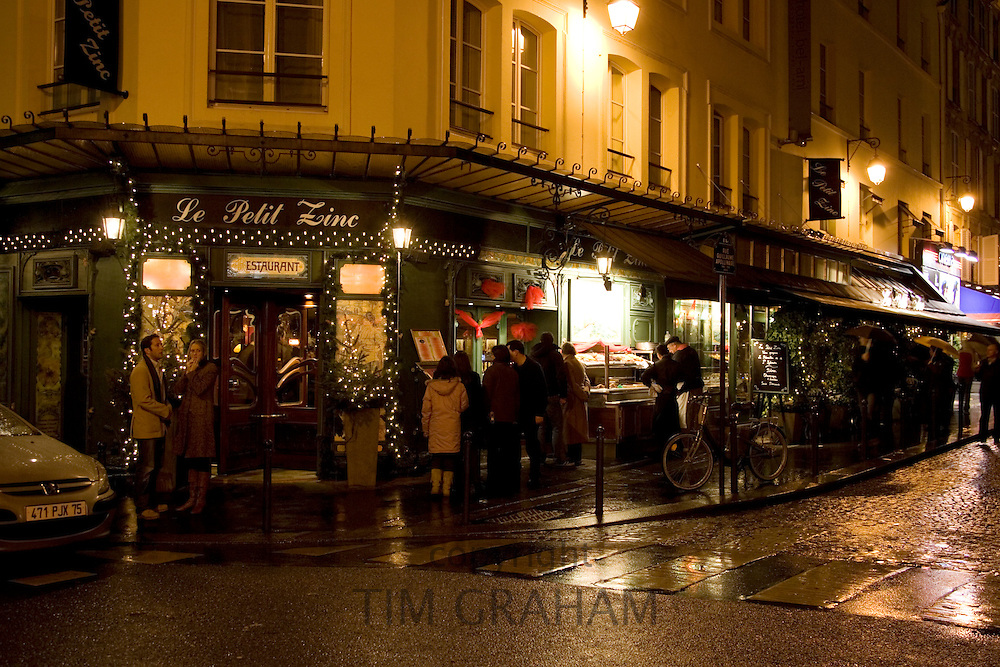 People shelter at night from rain on street corner and read menu outside Le Petit Zinc Restaurant, Left Bank, Paris, France