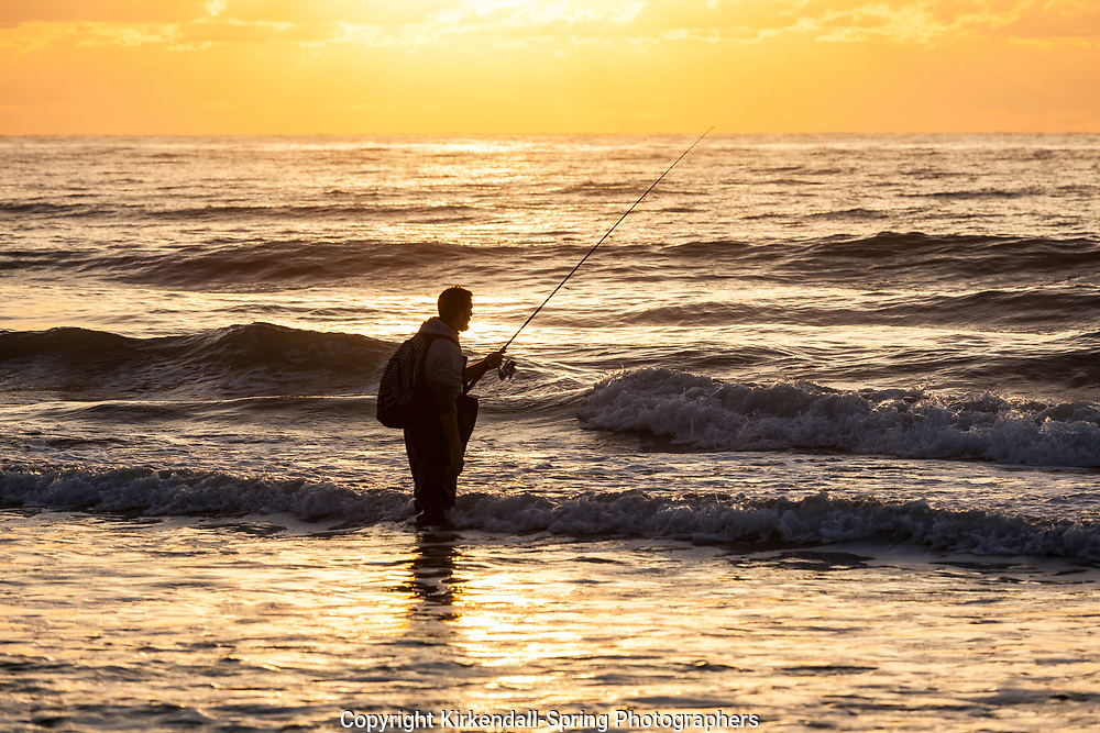 NC00912-00...NORTH CAROLINA - Surf fishing during sunrise over the Atlantic Ocean at the Surf City Pier.