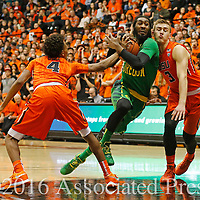 Oregon's Dwanye Benjamin, center, drives between Oregon State's Derrick Bruce, left, and Tres Tinkle, right, in the first half of an NCAA college basketball game, in Corvallis, Ore., on Sunday, Jan. 3, 2016. (AP Photo/Timothy J. Gonzalez)