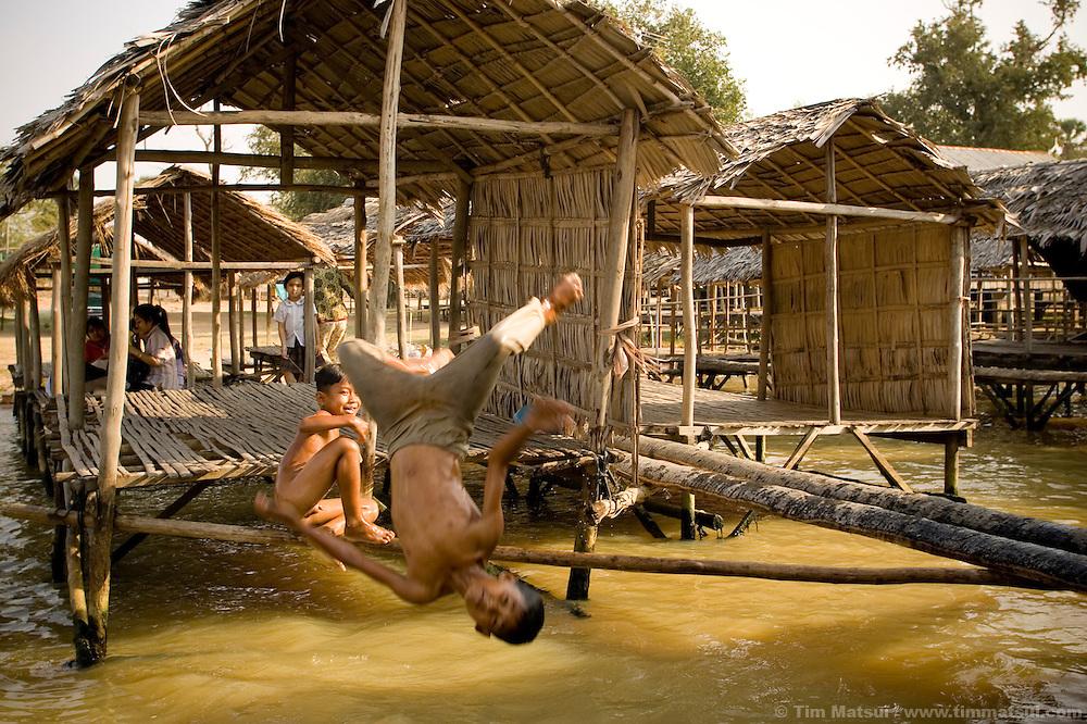 Beggar children play and eat scraps at Tonle Bati, a lake near Phnom Penh, Cambodia.