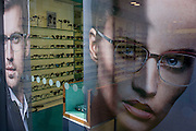 An optician's window ad faces and spectacles display in central London.