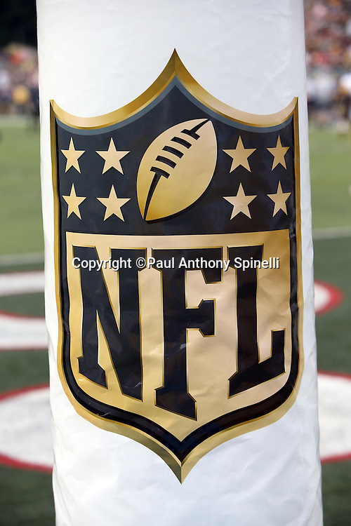 The NFL shield is colored black and gold in honor of the NFL's 50th year of Super Bowls as it is displayed on an end zone goal post for the Pittsburgh Steelers 2015 NFL Pro Football Hall of Fame preseason football game against the Minnesota Vikings on Sunday, Aug. 9, 2015 in Canton, Ohio. The Vikings won the game 14-3. (©Paul Anthony Spinelli)