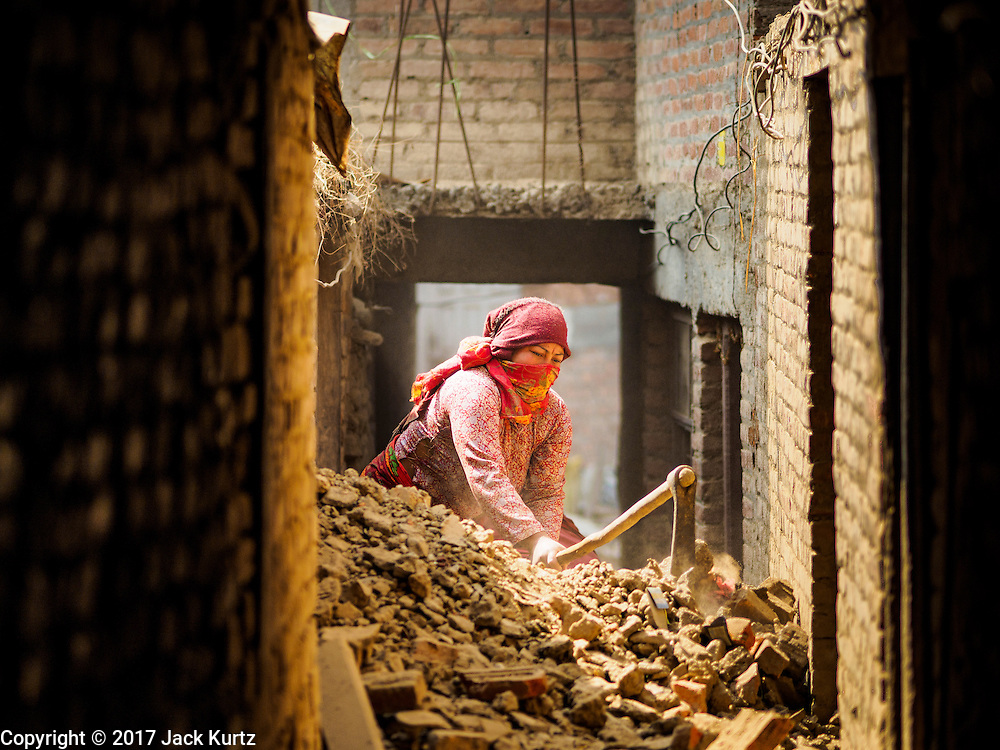 01 MARCH 2017 - BUNGAMATI, NEPAL: Laborers dig out a home in Bungamati destroyed in the 2015 earthquake. Recovery seems to have barely begun nearly two years after the earthquake of 25 April 2015 that devastated Nepal. In some villages in the Kathmandu valley workers are working by hand to remove ruble and dig out destroyed buildings. About 9,000 people were killed and another 22,000 injured by the earthquake. The epicenter of the earthquake was east of the Gorka district.     PHOTO BY JACK KURTZ