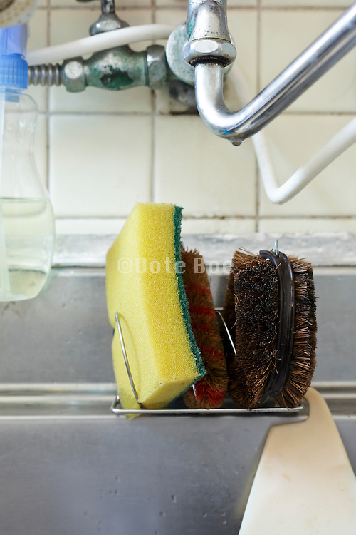 kitchen sink close up with various brush scrubbers sponge