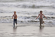 Brother and sister playing in the ocean waves on the coast of Washington at Ocean Shores