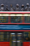 London bus passes Women of World War II memorial, England, United Kingdom