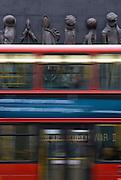 London bus passes Women of World War II memorial, England, United Kingdom