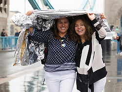 © Licensed to London News Pictures. 10/08/2018. London, UK.  Tourists shelter under a rain poncho during a heavy rain shower and wet weather on Tower Bridge at lunchtime today.  Photo credit: Vickie Flores/LNP