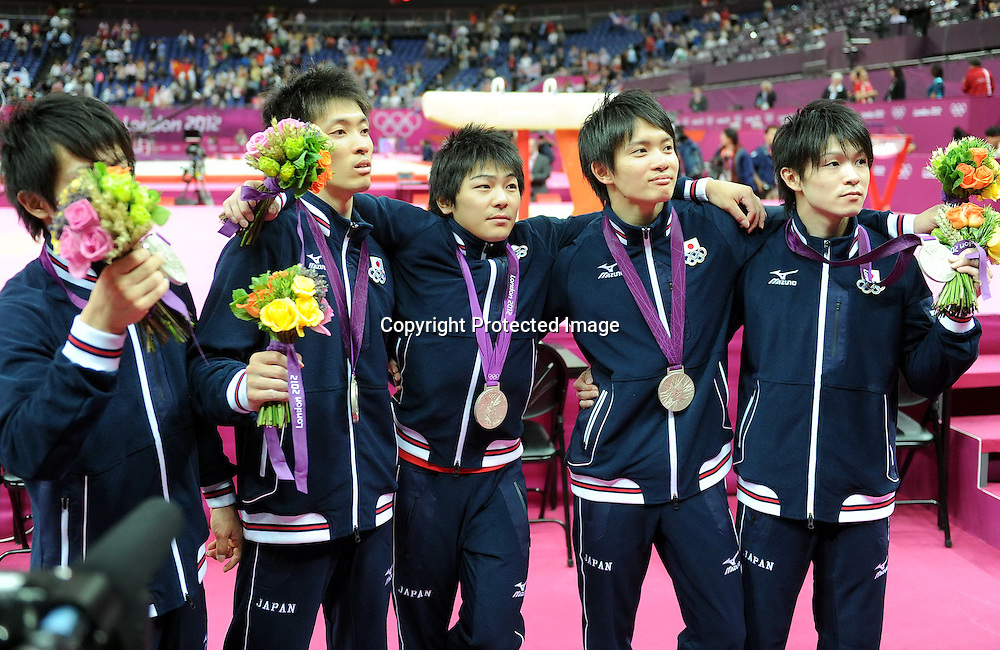 Jul 30, 2012; London, ENGLAND; Silver medalists Kohei Uchimura, Yusuke Tanaka, Koji Yamamuro, Kazuhito Tanaka and Ryohei Kato of Japan, gold medalists Zhe Feng, Weiyang Guo, Yibing Chen, Chenglong Zhang and Kai Zou of China and bronze medalists Daniel Purvis, Max Whitlock, Louis Smith, Kristian Thomas and Sam Oldham of Great Britain pose on the podium during the medal ceremony in the Artistic Gymnastics Men's Team final on Day 3 of the London 2012 Olympic Games at North Greenwich Arena.