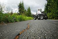 Bob Boyd sits on his ATV Tuesday on a stretch of Red Hawk Trail that leads to his home overlooking Hayden Lake. Logging trucks used in clear property near his home have caused damage to the road which Boyd says he can't afford to repair.