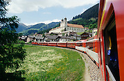 Glacier Express passing the 1000 year old monastery of Disentis.