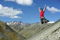 Man jumping down rocky slope with arms raised