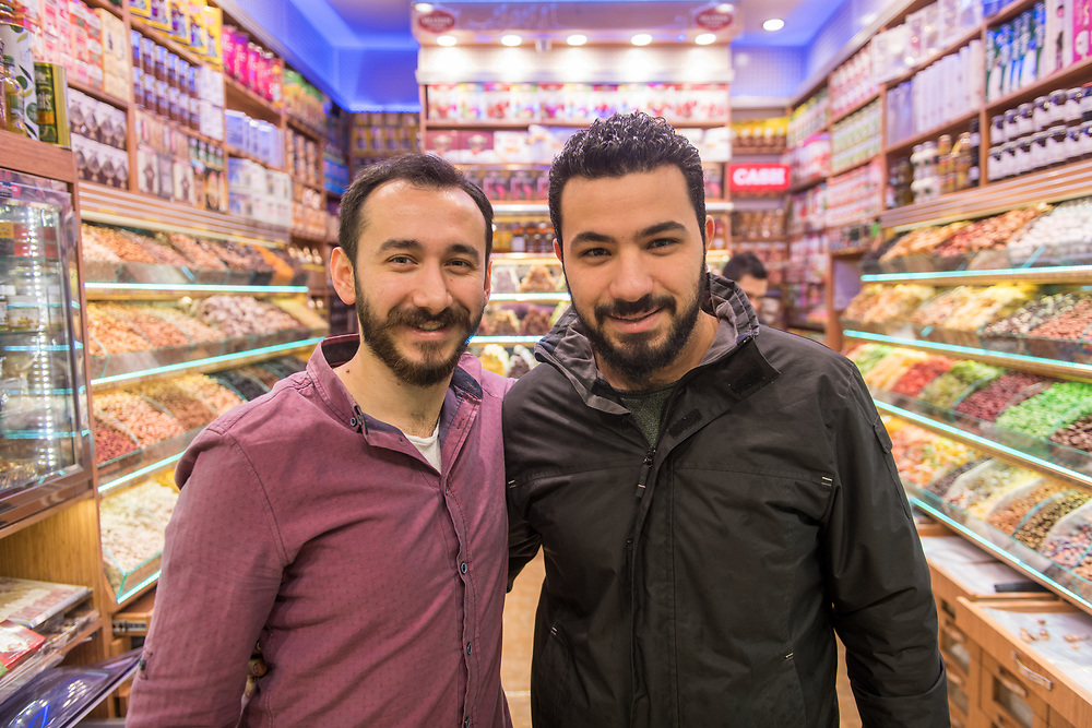 Two Adult males smile and poses for photo together inside a sweets and dried goods shop, Istanbul Spice bazaar in Turkey