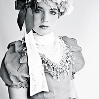 Close up of a young female wearing white lace with floral headband looking at camera
