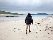 Woman walking overcast sky sandy beach Eoligarry, Barra, Outer Hebrides, Scotland, UK