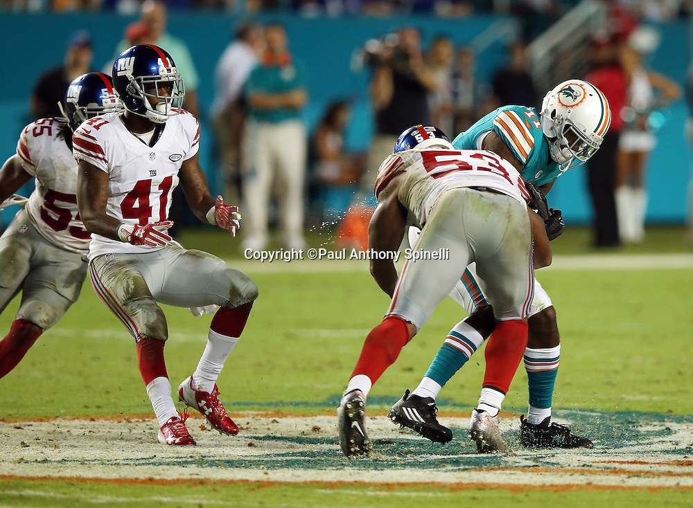 Miami Dolphins wide receiver DeVante Parker (11) is chased by New York Giants cornerback Dominique Rodgers-Cromartie (41) and New York Giants outside linebacker J.T. Thomas III (55) as he gets tackled by New York Giants middle linebacker Jasper Brinkley (53) as he catches a fourth quarter pass during the NFL week 14 regular season football game against the New York Giants on Monday, Dec. 14, 2015 in Miami Gardens, Fla. The Giants won the game 31-24. (©Paul Anthony Spinelli)