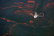 Louisiana (USA). May 5th, 2010. Aerial view of the oil leaked from the Deepwater Horizon wellhead, slowly approaching the coast of Louisiana East of the mouth of the Mississippi river.   A BP leased oil platform exploded April 20 and sank after burning. Leaking an estimate of more than 200,000 gallons of crude oil per day from the broken pipeline to the sea. Eleven workers are missing, presumed dead. In the picture shrimp boat participating in the cleaning operation.Photo by Daniel Beltra/Greenpeace