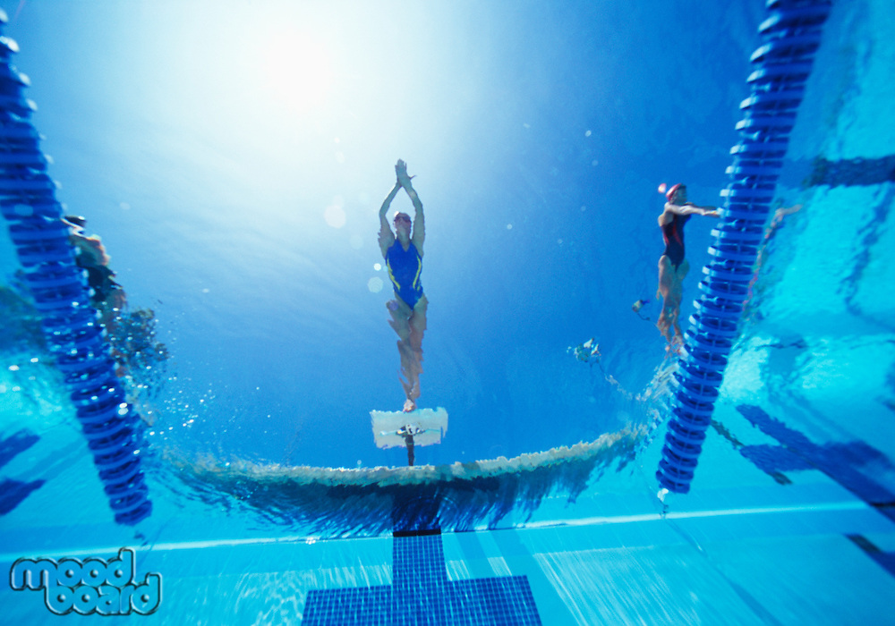 View of female swimmer diving in swimming pool