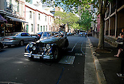 An antique open-top sedan carrying a wedding party drives past--The Rocks is a very popular setting for weddings in Sydney. The Rocks, Sydney, Australia