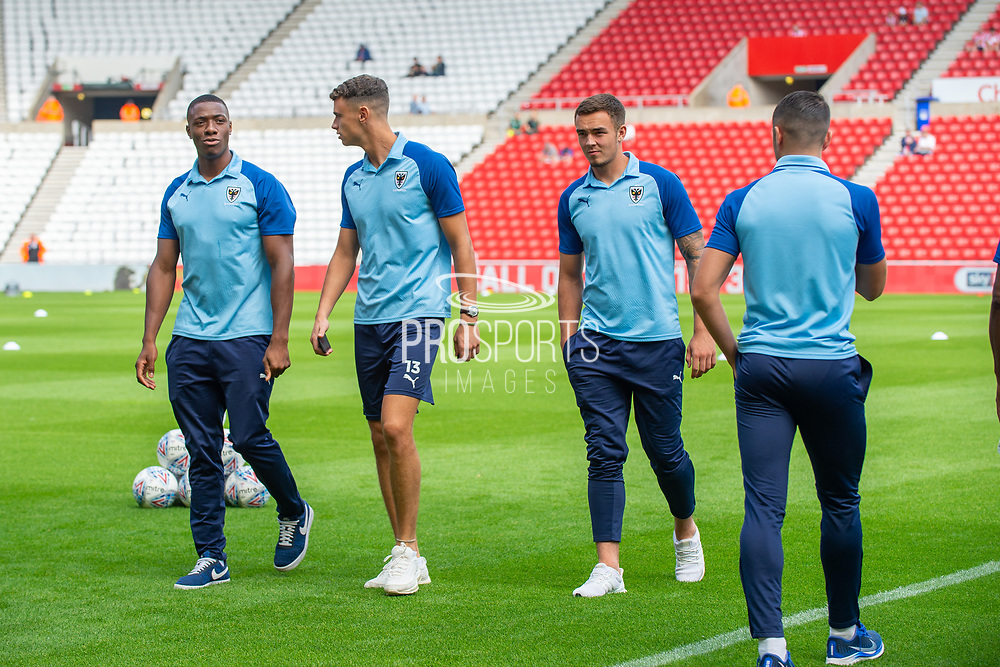 AFC Wimbledon players Paul Kalambayi (#30) and Nikola Tzanev (#13) of AFC Wimbledon on the pitch before the EFL Sky Bet League 1 match between Sunderland and AFC Wimbledon at the Stadium Of Light, Sunderland, England on 24 August 2019.