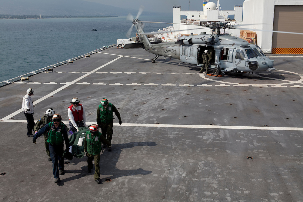 A Haitian earthquake victim is loaded off an MH-60S helicopter after being air-lifted to the USNS Comfort, a naval hospital ship, for treatment on Wednesday, January 20, 2010 in Port-Au-Prince, Haiti. The Comfort deployed from Baltimore, bringing nearly a thousand medical personnel to care for victims of Haiti's recent earthquake.