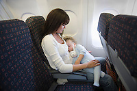 Mother and toddler on an aeroplane with the window blind down. The toddler is asleep cuddling a toy rabbit  while the mother looks at them