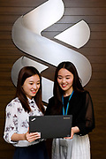 SHANGHAI, CHINA - MAY 13: Standard Chartered bank employees Anlan Cai (left) and Doris Zheng chat in Standard Chartered tower in Pudong Luziajui business district, on May 13, 2015, in Shanghai, China. (Photo by Lucas Schifres/Pictobank)