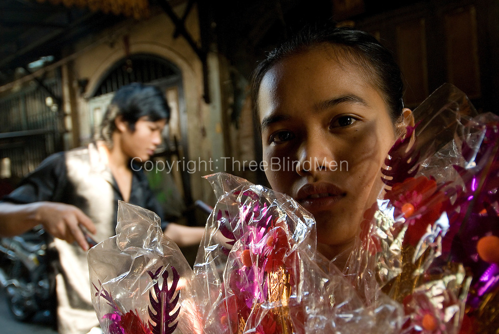 Girl with artificial flowers working in store in Chinatown.