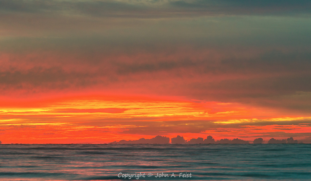 The sky turns brilliant as the sun climbs up in the sky.  The clouds out to sea create the image of structures rising out of the water.