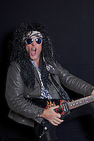 Senior rock guitarist performing over black background