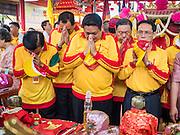 "23 JUNE 2015 - MAHACHAI, SAMUT SAKHON, THAILAND: Community leaders in Mahachai pray before taking the City Pillar Shrine out for the procession through town. The Chaopho Lak Mueang Procession (City Pillar Shrine Procession) is a religious festival that takes place in June in front of city hall in Mahachai. The ""Chaopho Lak Mueang"" is  placed on a fishing boat and taken across the Tha Chin River from Talat Maha Chai to Tha Chalom in the area of Wat Suwannaram and then paraded through the community before returning to the temple in Mahachai.   PHOTO BY JACK KURTZ"