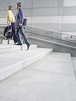 Business people walking up steps outdoors side view