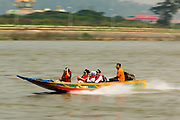 26 APRIL 2014 - CHAING SAEN, CHIANG RAI, THAILAND: Chinese tourists ride a high speed boat in the Mekong River in the Golden Triangle, a village in Chaing Saen district of Chiang Rai province, Thailand. The Golden Triangle is where Thailand, Myanmar (Burma) and Laos meet on the Mekong River. Chinese businesses play an increasingly important role in the Chiang Rai economy. Consumer goods made in China are shipped to Thailand while agricultural products made in Thailand are shipped to China. Large Chinese cargo boats ply the Mekong River as far south as Chiang Saen in the dry season and Chiang Khong when river levels go up in the rainy season.      PHOTO BY JACK KURTZ
