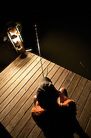 ANGLER FISHING FROM A DOCK AT NIGHT