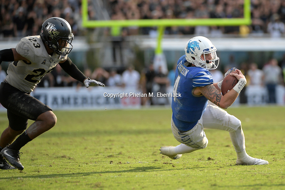 Memphis quarterback Riley Ferguson (4) scrambles for yardage in front of Central Florida defensive back Tre Neal (23) during the second half of the American Athletic Conference championship NCAA college football game Saturday, Dec. 2, 2017, in Orlando, Fla. Central Florida won 62-55. (Photo by Phelan M. Ebenhack)
