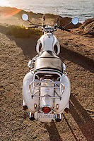 Rear view of a 1960s BMW R60US motorcycle (PR) parked overlooking the Pacific Ocean in Sonoma County California.