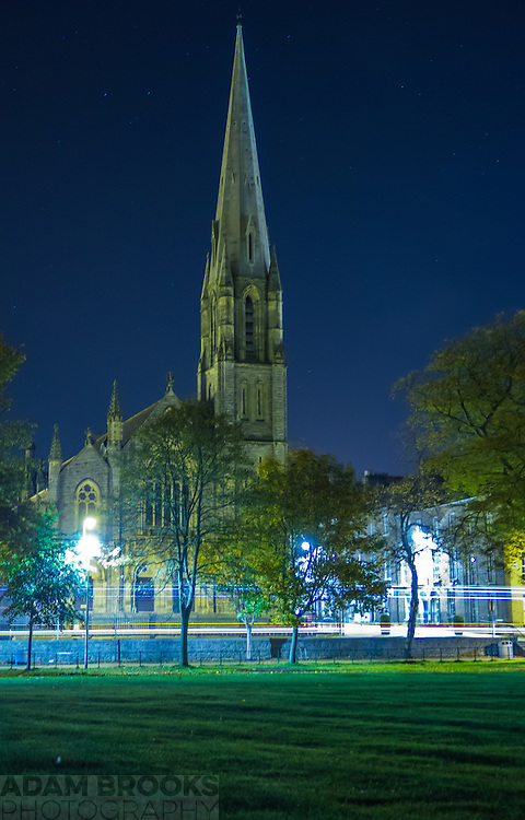 Armagh First Presbyterian Church viewed from the Mall at night, softly lit by the ambient night light of Armagh with headlight trails in the foreground.