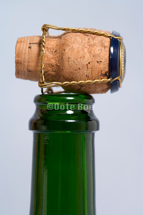 opened champagne bottle with cork placed on top of it