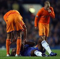 Photo: Paul Thomas.<br /> Chelsea v Barcelona. UEFA Champions League, Group A. <br /> 18/10/2006.<br /> <br /> Didier Drogba (Blue) of Chelsea lays injured on the ground by Edmilson (L).