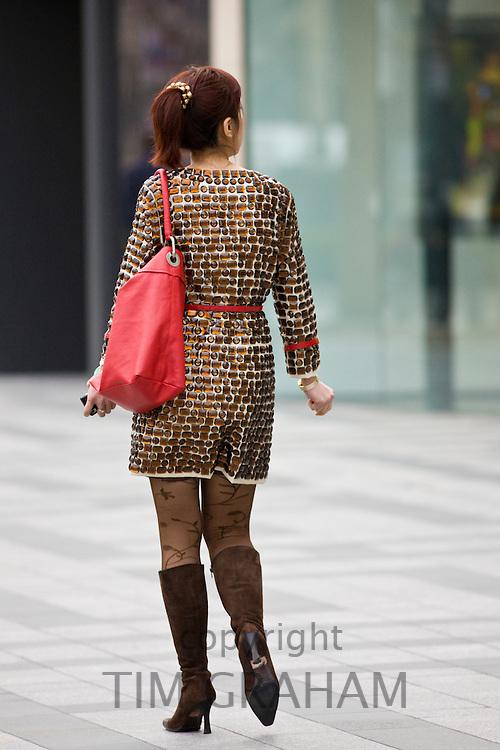 Woman walking on Nanjing Road, central Shanghai, China